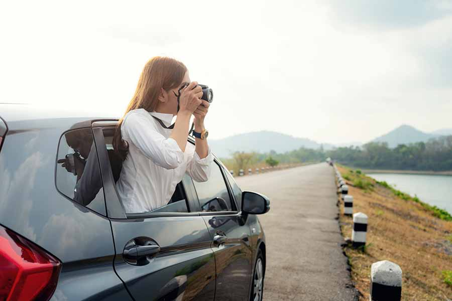 lady leaning out of rented car to take photos