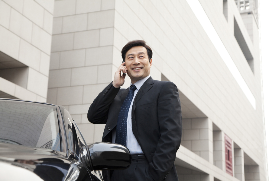 Businessman making a call outside car