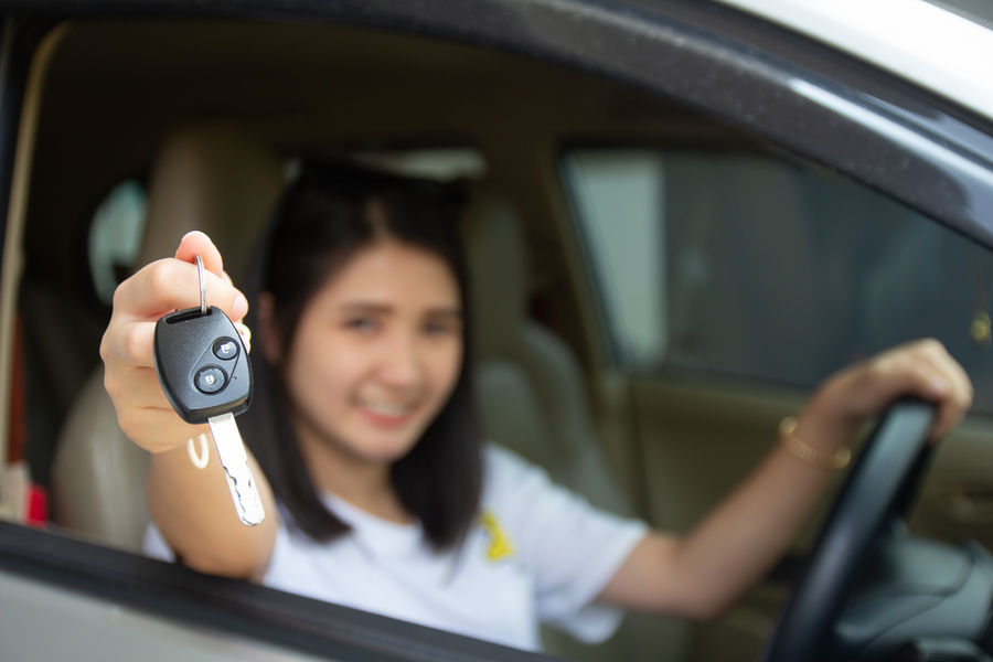Woman holding key from car rental in singapore
