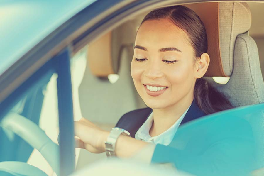 smiling lady checking her watch in her rented car